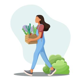 Bella ragazza con una scatola di verdure fresche.