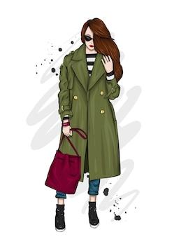 Bella ragazza in un elegante cappotto, pantaloni e occhiali.