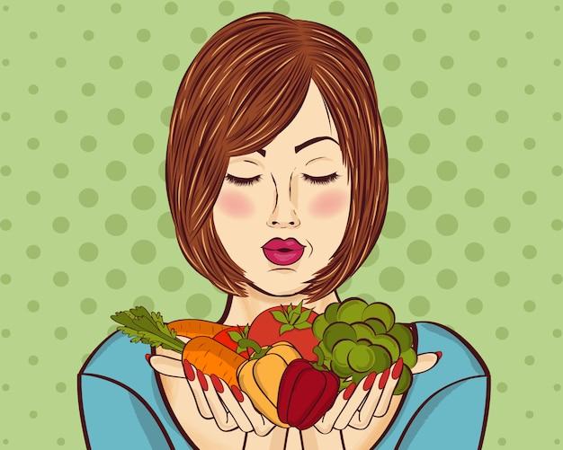Bella signora dai capelli rossi con verdure nelle sue mani