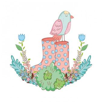 Bellissimo uccello con stivali da giardinaggio e cespuglio