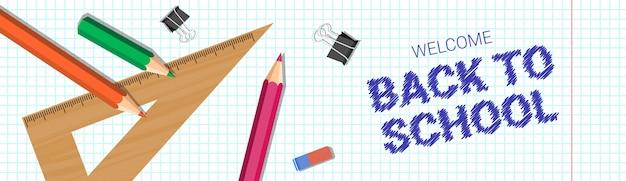 Bentornato a scuola poster matite colorate gomma e righelli sul quaderno a quadri b