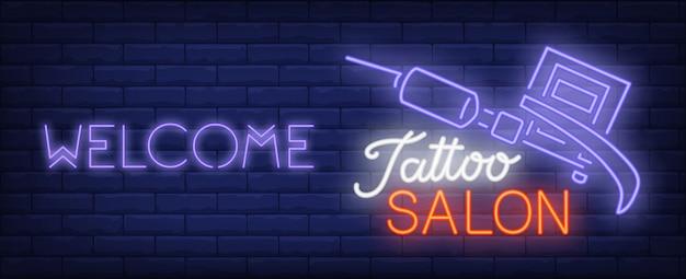 Benvenuti al segno al neon del salone del tatuaggio. macchina da tatuaggio professionale e scritta brillante