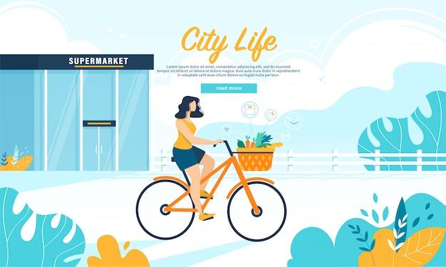 Bici di giro della giovane donna con l'insegna della merce nel carrello dell'alimento sano