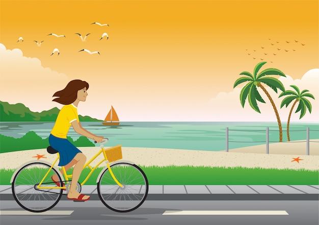 Bicicletta di guida della ragazza in spiaggia