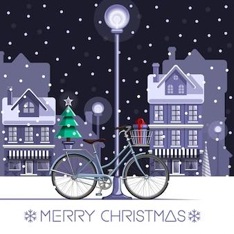 Bicicletta invernale con albero di capodanno e confezione regalo. buon natale. sfondo festivo con bicicletta decorata su uno sfondo di città notturna innevata.