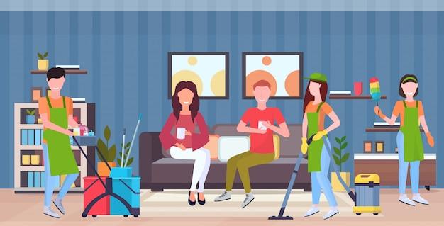 Bidelli pulitori di squadra in uniforme che lavorano insieme a attrezzature professionali concetto di servizio di pulizia coppia seduta sul divano moderno salotto interno piano integrale orizzontale