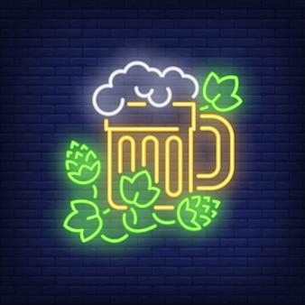 Boccale di birra con l'insegna al neon della pianta del luppolo