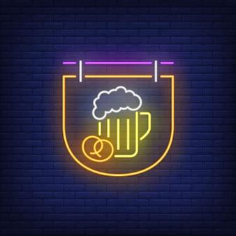 Boccale di birra e ciambellina salata sull'insegna al neon dell'insegna.