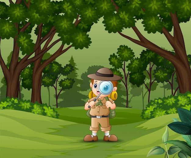 Boy explorer con lente di ingrandimento nella foresta