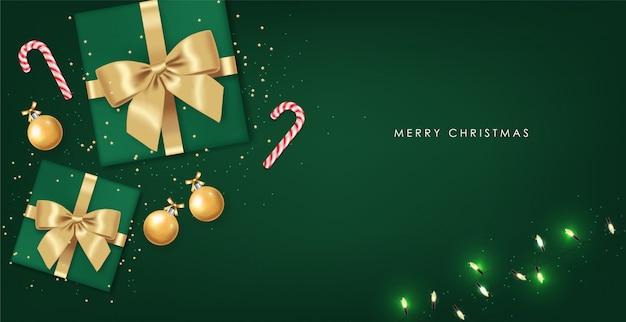 Buon natale, elementi di design decorativo, inverno, sfondo di celebrazione, luci realistiche, caramelle di natale, palla d'oro e regalo con fiocco, sfondo verde