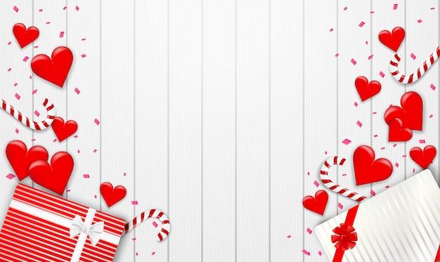 Buon san valentino sullo sfondo. con cuore, confezione regalo e coriandoli di stagnola rosa su fondo di legno bianco. .