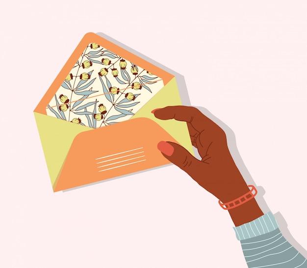 Busta postale con stampa floreale in mano di una ragazza.