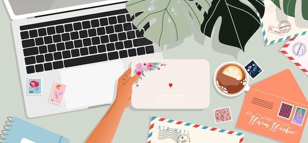Buste, laptop e cartoline sul tavolo. mani in possesso di una busta. vista dall'alto verso il basso. biglietto di auguri e una lettera in una mano. illustrazione moderna per il web design e la stampa.