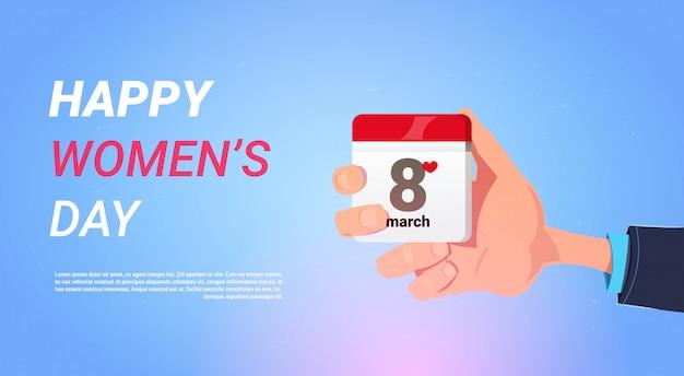 Calendario felice della tenuta della mano dell'uomo dell'insegna di festa di giorno delle donne con il concetto di 8 marzo