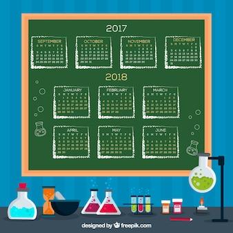 Calendario scolastico sulla lavagna con materiali scientifici