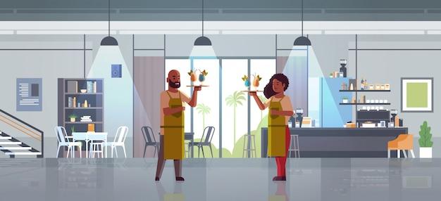 Camerieri che tengono vassoi con cocktail