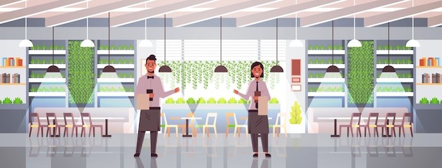 Camerieri professionisti coppie che tengono il menu calorosamente accogliente al ristorante accogliente