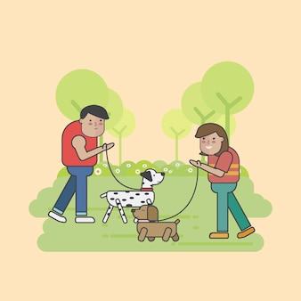 Camminatori del cane che si incontrano nel parco