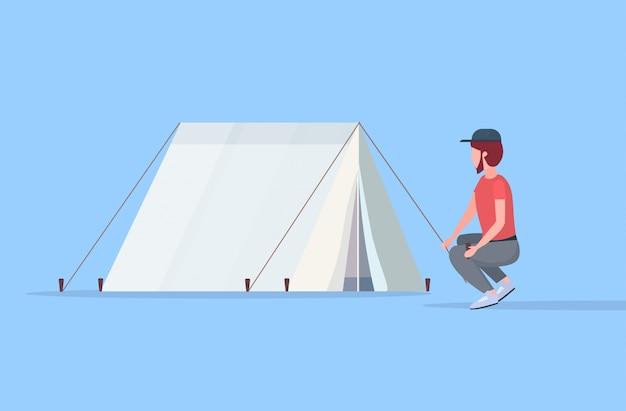Camper escursionista uomo l'installazione di una tenda preparando per il campeggio escursionismo concetto viaggiatore su escursione orizzontale personaggio dei cartoni animati maschio a figura intera piatta