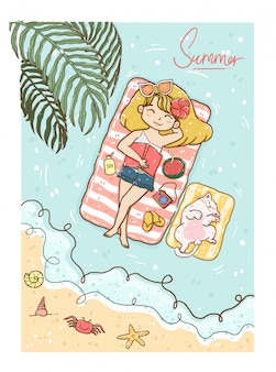Capelli gialli della ragazza sveglia in bikini e jeans che prendono il sole sul mare con il gatto di gattino lanuginoso bianco nell'ora legale