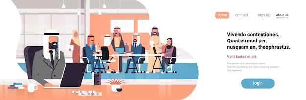 Capo arabo dell'uomo facendo uso dell'insegna del posto di lavoro del computer portatile