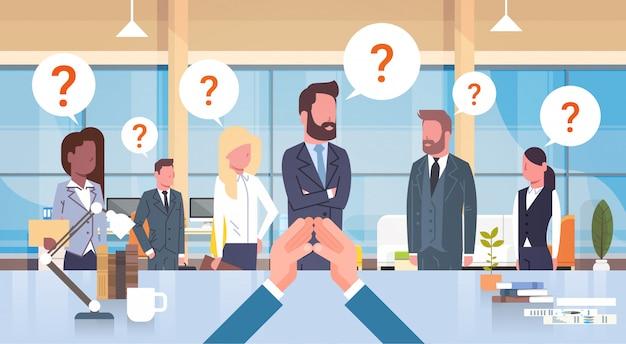 Capo dell'uomo d'affari che esamina la sua squadra di affari con theseion mark sitting at desk, capo with group
