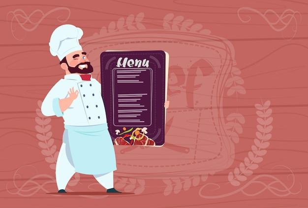 Capo sorridente del fumetto del menu del ristorante di holding del cuoco del cuoco unico in uniforme bianca sopra fondo strutturato di legno