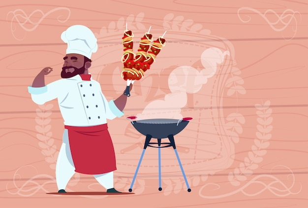 Capo sorridente del ristorante del fumetto del cuoco unico afroamericano di hold kebab in uniforme bianca sopra fondo strutturato di legno
