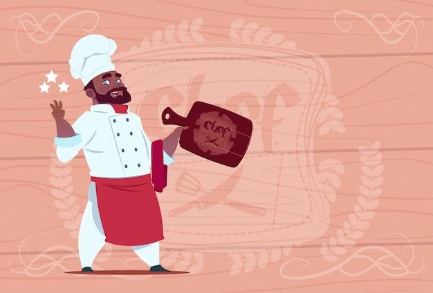 Capo sorridente del ristorante del fumetto del cuoco unico afroamericano hold star award in uniforme bianca sopra fondo strutturato di legno