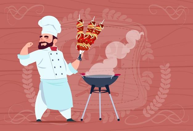 Capo sorridente del ristorante del fumetto di hold kebab del cuoco del cuoco unico in uniforme bianca sopra fondo strutturato di legno