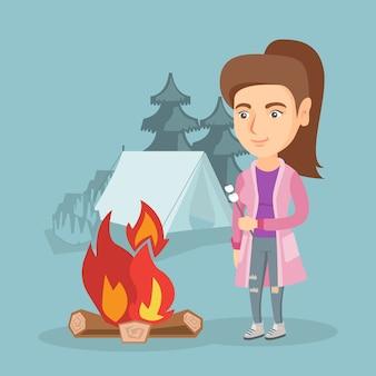 Caramella gommosa e molle di torrefazione caucasica della donna sopra il fuoco di accampamento