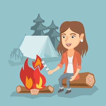 Caramella gommosa e molle di torrefazione caucasica della ragazza sopra il fuoco di accampamento.