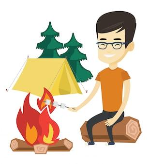 Caramella gommosa e molle di torrefazione della donna sopra il fuoco di accampamento.