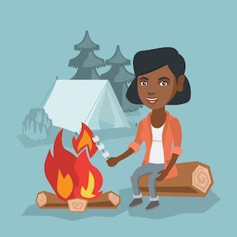 Caramella gommosa e molle di torrefazione della ragazza africana sopra il fuoco di accampamento.