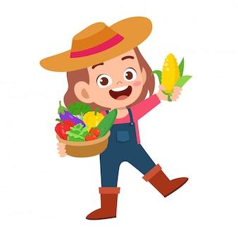 Carino bambino felice raccoglie frutta e verdura
