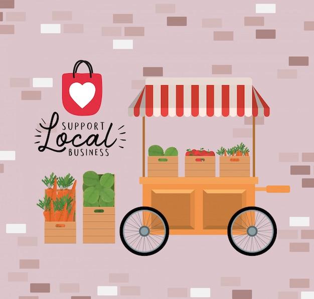 Carrello con verdure all'interno di scatole e supporto alle attività locali