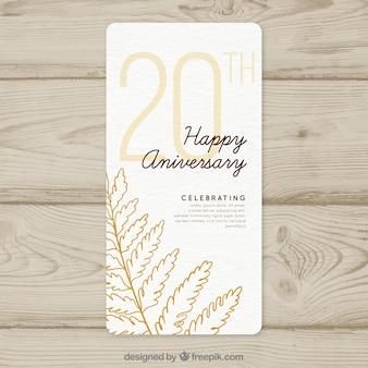 Carta di anniversario di matrimonio con stile disegnato di foglie in mano