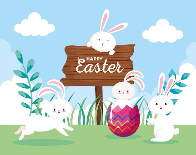 Carta di pasqua felice con i conigli nel paesaggio