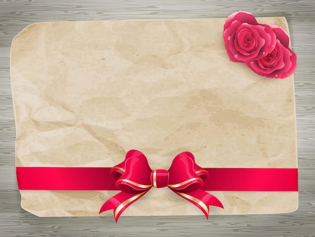 Carta di san valentino con fiocco rosso e coppia di cuori su fondo di legno.