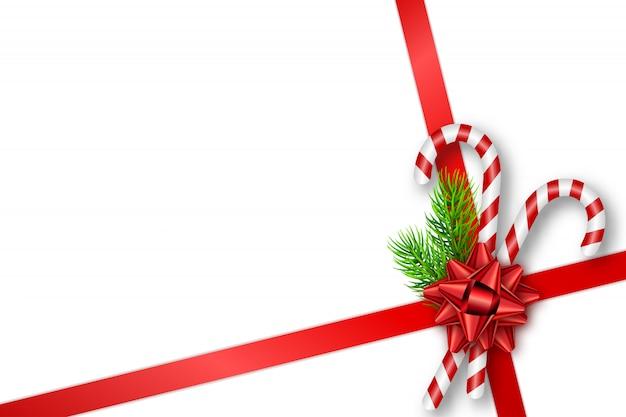 Carta regalo di natale con fiocco, rami, bastoncini di zucchero