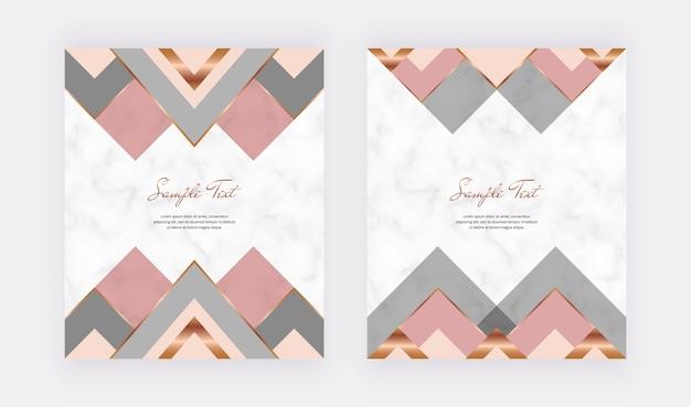 Carte geometriche con linee rosa, dorate e forme triangolari sul marmo.