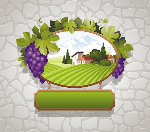 Cartello vintage con uva e immagine del paesaggio di campagna contro un muro di pietra