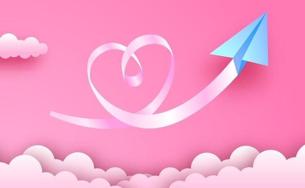 Cartolina d'auguri di san valentino e concetto di amore. stile di arte di carta con aeroplano di carta origami blu con nuvole e amore come il modo di carta di forma sullo sfondo del cielo rosa