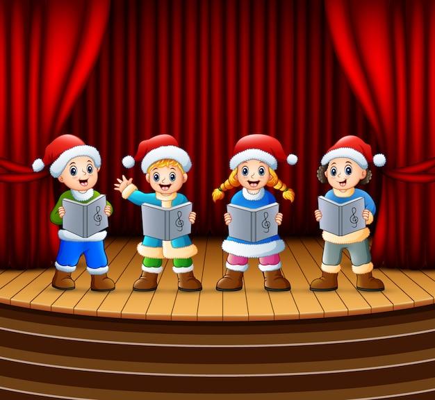Cartoon bambini cantando canti di natale sul palco
