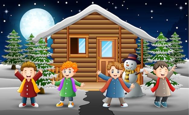 Cartoon bambini cantando davanti alla casa nevica