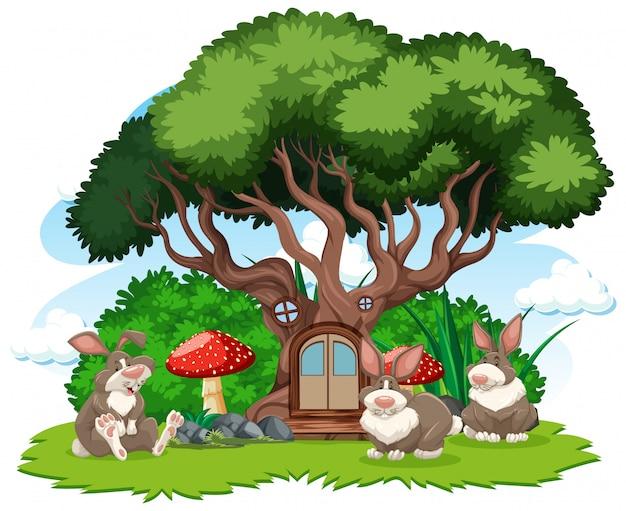 Casa sull'albero con uno stile del fumetto di tre conigli su fondo bianco