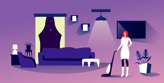 Casalinga che usando la donna dell'aspirapolvere che fa interno moderno moderno del salone di concetto di famiglia di cura del pavimento di lavori domestici