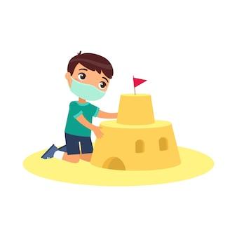 Castello sveglio della sabbia della costruzione del bambino con una maschera. protezione da virus, concetto di allergie. bambino divertente che gioca sul personaggio dei cartoni animati della spiaggia. ragazzino che costruisce fortezza sabbiosa