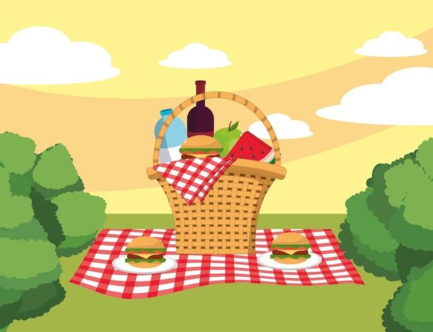 Cestino con hamburger e bottiglia di vino nella tovaglia