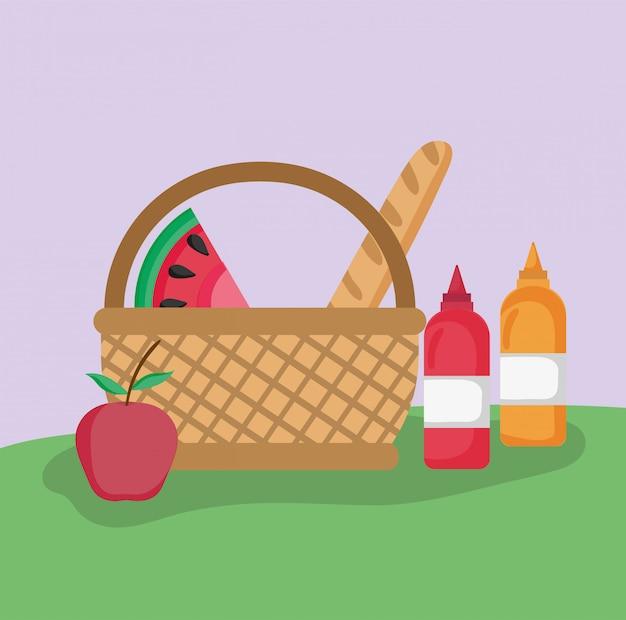 Cestino di vimini pane di frutta e salse picnic nel parco